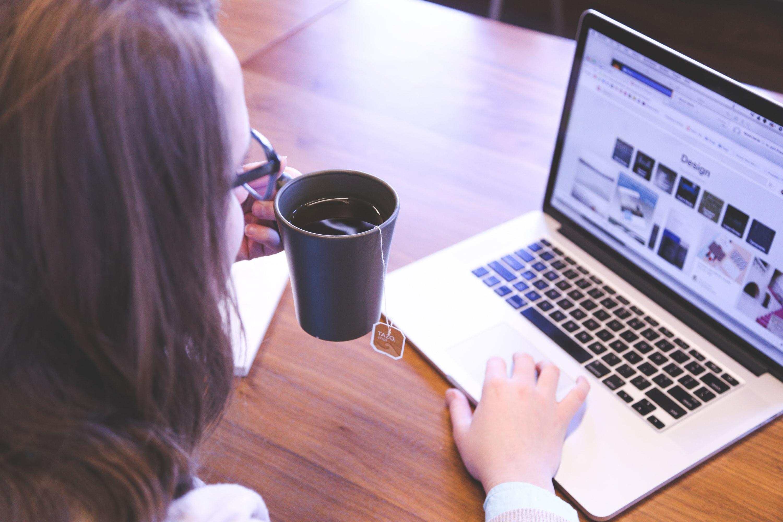 コーヒーを飲みながらパソコンを見る女