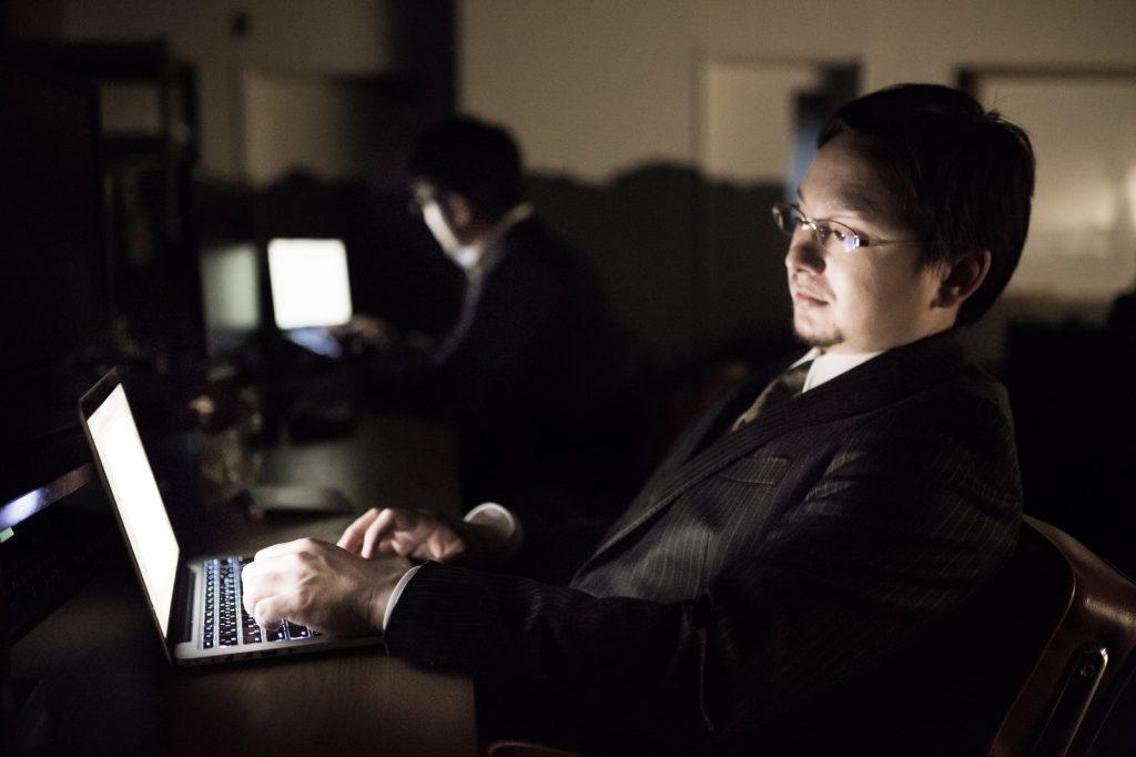 暗闇の中でパソコンに触る男