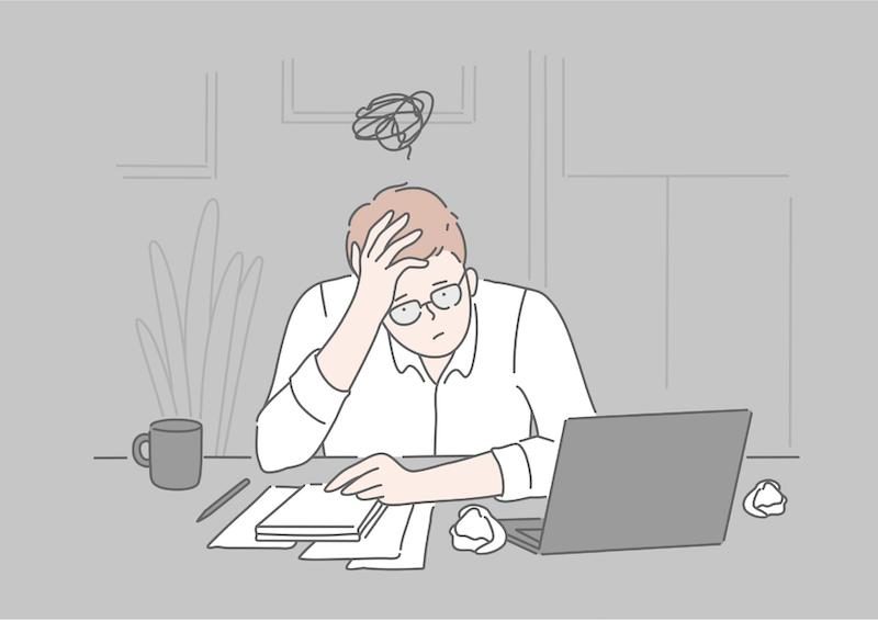 パソコンの前で悩んでいる男性
