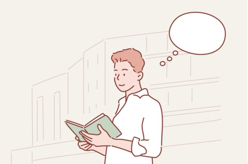 本を読みながら考えごとをする男性